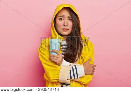 Photo Of Dissatisfied Asian Woman Smirks Face, Keeps Arms Crossed, Trembles From Being Cold After Wa