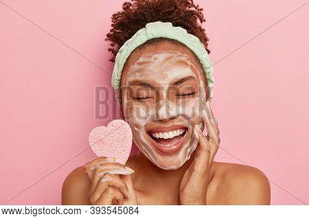 Relaxed Joyful Dark Skinned Female Model Washes Face With Soap Bubbles, Enjoys Pampering Session, Ke