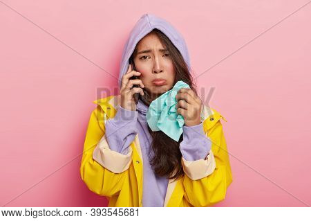 Photo Of Dissatisfied Sick Woman Holds Tissue, Caught Cold During Stroll Across Street On Rainy Day,