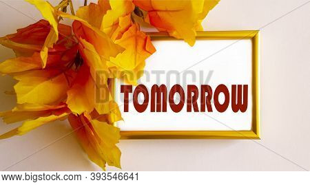 The Word Tomorrow Is Written In A Gold Frame Framed By Yellow Foliage On A Light Background