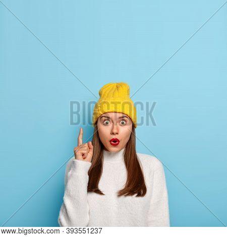Portrait Of Impressed Brunette Girl Indicates Above With Index Finger, Gasps From Wonder, Shows Blan