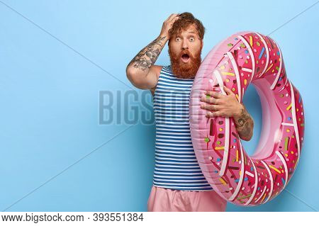 Studio Shot Of Scared Redhead Man Recreats During Summer Holidays, Holds Pink Swimring, Shocked To F