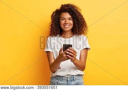 Happy Smiling Woman Holds Mobile Phone, Texts Message On Cellular, Surfes Internet, Has Curly Bushy