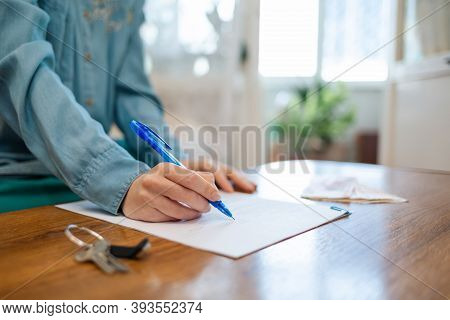 World Day Of The Lease. A Woman Signs Documents, Keys Are On The Table. Hands Close-up. Rent And Pur