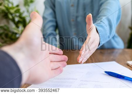 Realtor And Buyer Handshake. Close Up. There Are Documents On The Table. Rental And Purchase Of Real