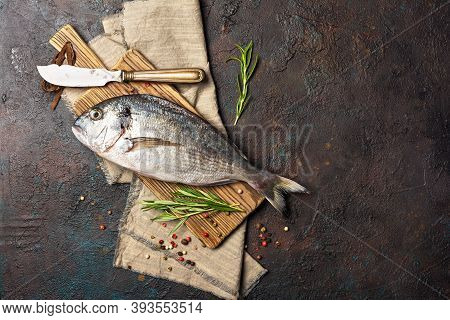 Fresh Fish Dorada Or Gilt-head Bream On Cutting Board With Spices And Knife