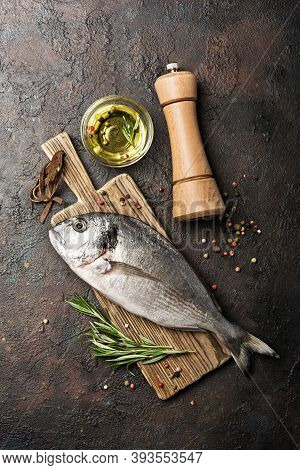 Fresh Fish Dorada Or Gilt-head Bream On Cutting Board With Spices And Olive Oil