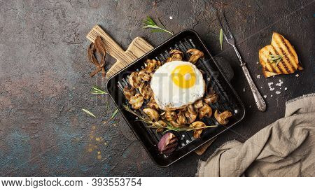 Fried Egg And Mushrooms On Grill Pan With Onion, Rosemary, Bread
