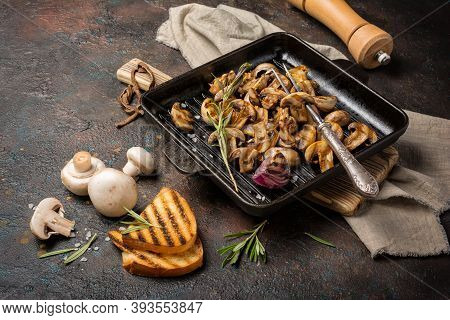 Spicy Fried Mushrooms On Grill Pan With Onion, Rosemary And Bread