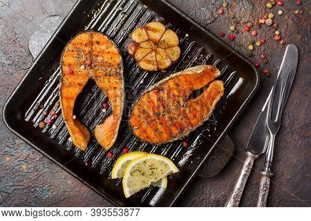 Spicy Fried Red Fish Salmon Steak On Grill Pan With Garlic And Lemon
