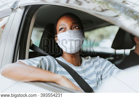 Woman with mask at drive thru with her car