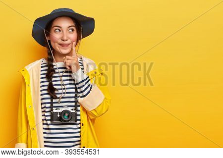 Pensive Female Tourist Keeps Index Finger On Cheek, Thinks What Way To Choose, Explores Local Surrou