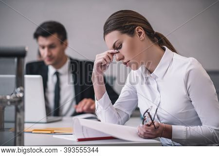 Woman In Profile Studying Document Sitting In Office