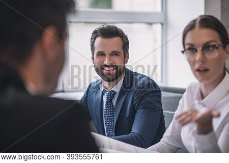 Gesturing Serious Woman, Smiling Man And Colleague Back
