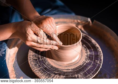 Women Hands. Potter At Work. Creating Dishes. Potters Wheel. Dirty Hands In The Clay And The Potters