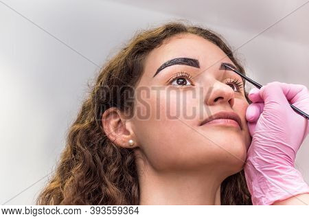 Portrait Of Young Beautiful Girl Whose Eyebrows Are Plucked. Eyebrow Shaping In A Beauty Salon. Clos