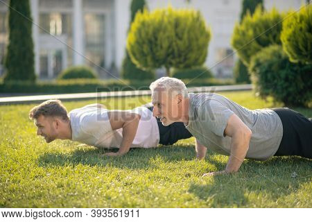 Young Brown-haired Male And Mature Grey-haired Male Doing Push Ups On Grass