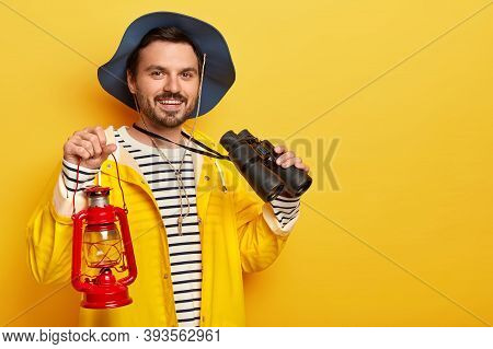 Photo Of Delighted Man With Stubble, Wears Headgear And Yellow Raincoat, Carries Kerosene Lamp And B