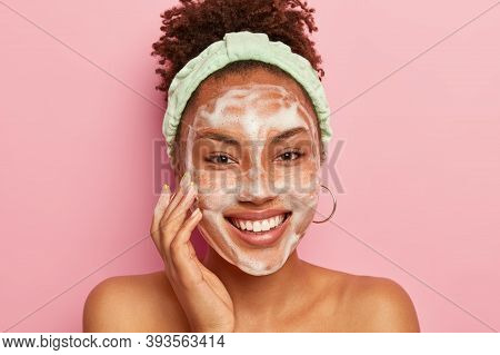 Teenage Skincare Concept. Optimistic Dark Skinned Lady Uses Foaming Cleanser For Washing Face, Smile