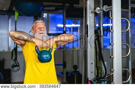 Senior Fit Man Doing Kettle Bell Exercises Inside Gym - Fit Mature Male Training In Wellness Club Ce