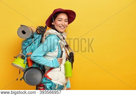 Happy Brunette Asian Traveler Carries Big Tourist Backpack, Uses Binoculars For Journey, Stands Agai