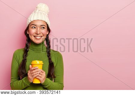 Portrait Of Pleasant Looking Young Korean Woman Holds Coffee Cup, Warms During Cold Wet Day, Wears W