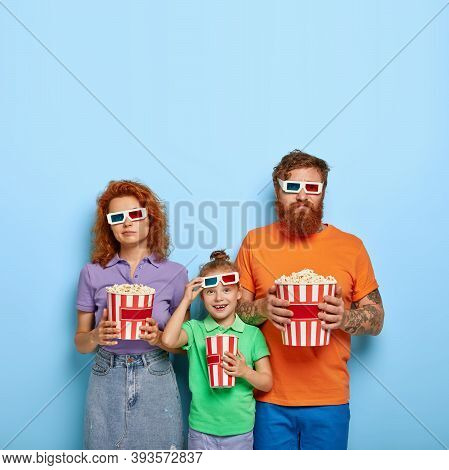 Isolated Shot Of Happy Small Redhead Girl Takes Off Cinema Glasses, Dressed In Green T Shirt, Stands