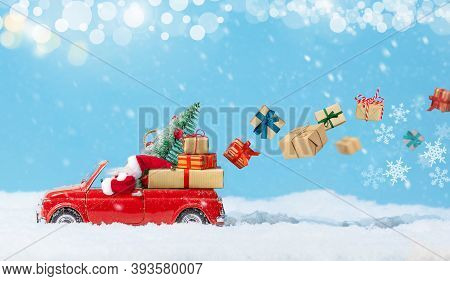 Santa Claus In Red Toy Car Delivering Christmas Presents Or New Year Gifts At Snowy Background. Holi