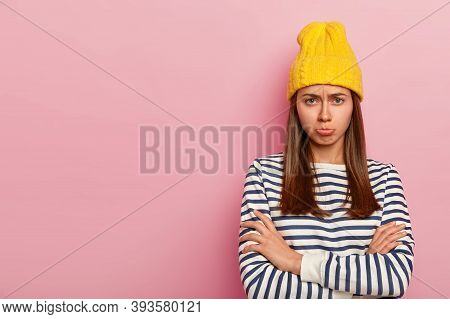 Pretty Offended Woman Looks With Sorrowful Expression, Frowns Face And Purses Lips With Displeasure,