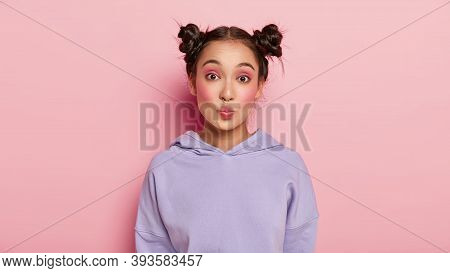 Facial Expressions Concept. Pretty Young Japanese Woman With Funny Look, Keeps Lips Rounded, Has Two