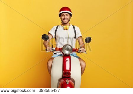 Image Of Positive Male Rides Scooter On Road Through City, Wears Helmet, White T Shirt, Being In Goo