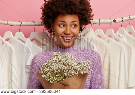 Lovely Pleased Woman Has Curly Hair, Being In Good Mood, Has Toothy Smile, Wears Casual Purple Jumpe