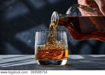 Round Glass Of Whiskey With Ice On A Concrete Table, A Glass Is Filled With Whiskey From A Bottle. A