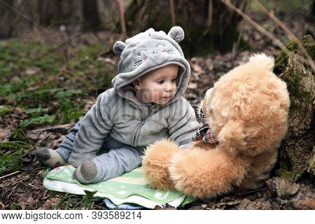 Kid In The Woods With A Teddy Bear. Little Child With A Toy Is Resting In The Park.