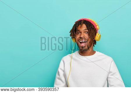 Music Is Always With Me. Positive Dark Skinned Youngster Has Dreadlocks, Gets Music Account Subscrip