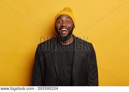 Shot Of Glad Plump Dark Skinned Man Laughs Positively, Smiles Joyfully, Rejoices Pleasant Meeting, W