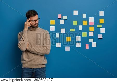 People, Work, Thoughts Concept. Contemplative Bearded Guy Keeps Finger On Temple, Looks Pensively As