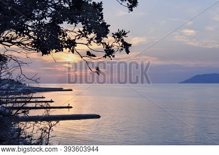 Dramatic Sunset With Beautiful Clouds And Tree On A Background. Piers And Mountains Blue Colored. Re