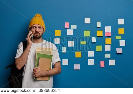 Handsome Hipster Calls Friend After Lectures, Returns From College, Stands With Textbooks And Rucksa