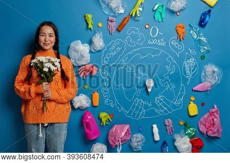 Satisfied Asian Woman With Two Pigtails, Wears Orange Jumper, Holds Bouquet, Cares For Nature, Being