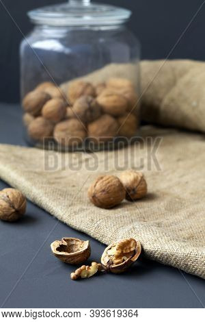 Walnuts. Unpeeled And Peeled Walnuts In Shells On A Black Table And In A Glass Jar. Brown Nuts With