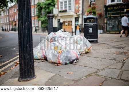 Plastic Bags Of Trash Abandoned On The Sidewalk Next To A Lamppost
