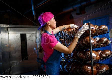 A Young Girl Works In A Bakery. She Puts Bread On A Shelf. Woman Baker At Workplace In A Bakery. A P