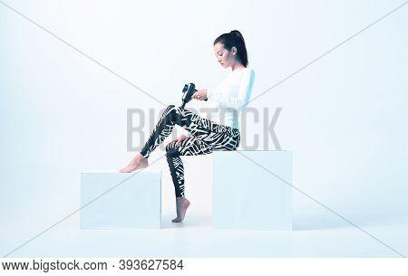 Athletic Young Female In Sportswear Massaging Leg By Handheld Massage Gun In Neon Light, Post-workou