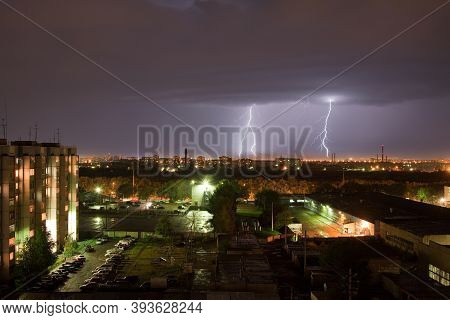 Powerful Thunderbolt Hits The City At Night. A Strong Lightning Strike Over A Dark Gray Sky Hits The