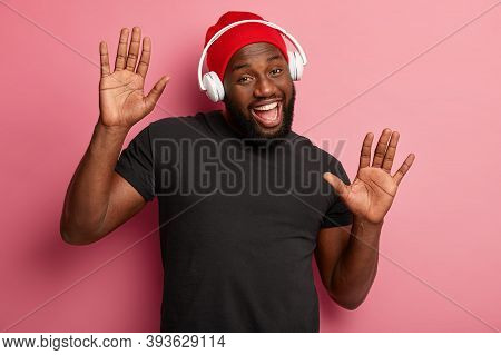 Satisfied Bearded Male Youngster Listens Merry Song In Headphones, Moves Over Pink Background, Boost