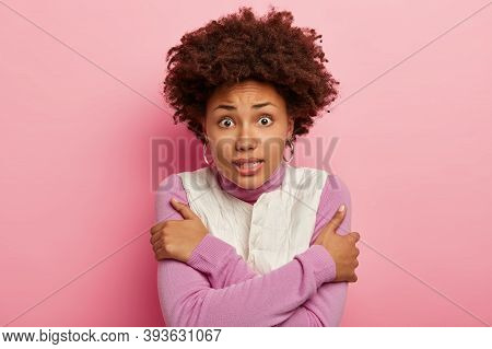 Shot Of Scared Young Girl Crosses Hands Over Chest, Trembles And Looks Puzzled At Camera, Feels Cold