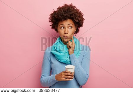 Afro American Curly Woman Keeps Index Finger On Cheek, Looks Thoughtfully Aside, Contemplates About
