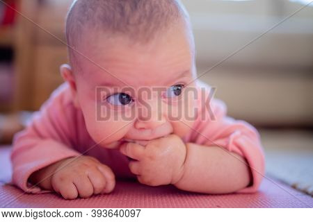 Baby Girl Lying Down On A Pink Rug With Her Fingers In Her Mouth