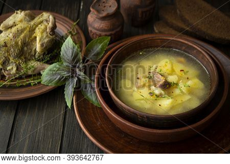Partridge Soup With Basil In A Rustic Bowl On Dark Wooden Table